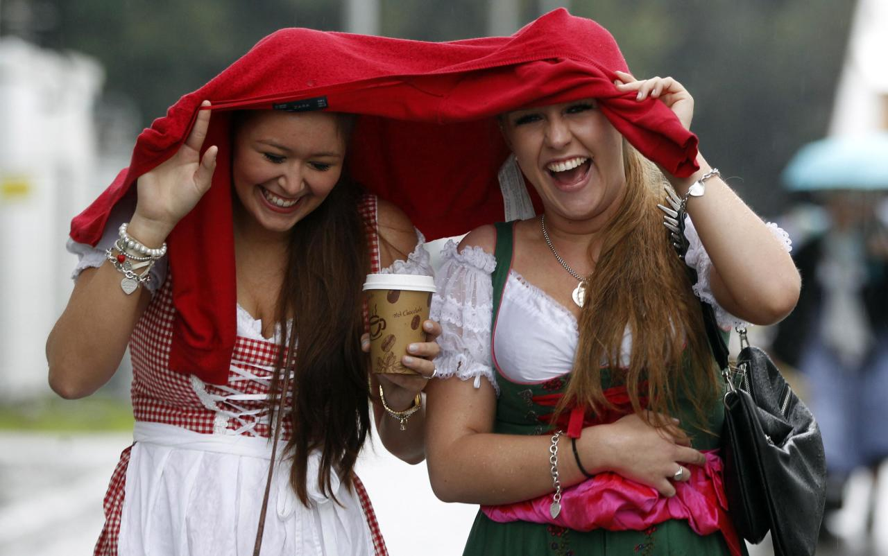 """Two women react, as they arrive for the opening of the famous Bavarian """"Oktoberfest"""" beer festival as rain falls, in Munich, southern Germany, Saturday, Sept. 22, 2012. The world's largest beer festival, to be held from Sept. 22 to Oct. 7, 2012 will see some million visitors. (AP Photo/Matthias Schrader)"""
