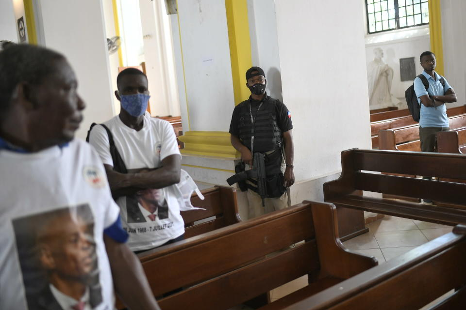 The city mayor's security guard stands by during a memorial service for slain Haitian President Jovenel Moïse in the Cathedral of Cap-Haitien, Haiti, Thursday, July 22, 2021. Moïse was killed in his home on July 7. (AP Photo/Matias Delacroix)