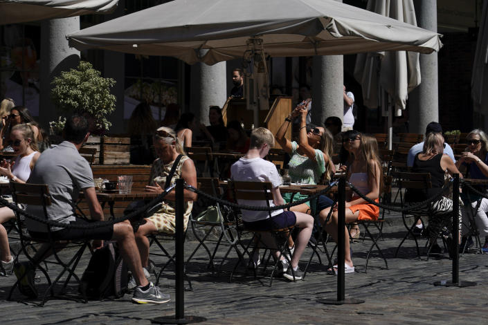 People sit at outside tables in Covent Garden, London, Monday, June 14, 2021. British Prime Minister Boris Johnson is expected to confirm Monday that the next planned relaxation of coronavirus restrictions in England will be delayed as a result of the spread of the delta variant first identified in India. (AP Photo/Alberto Pezzali)