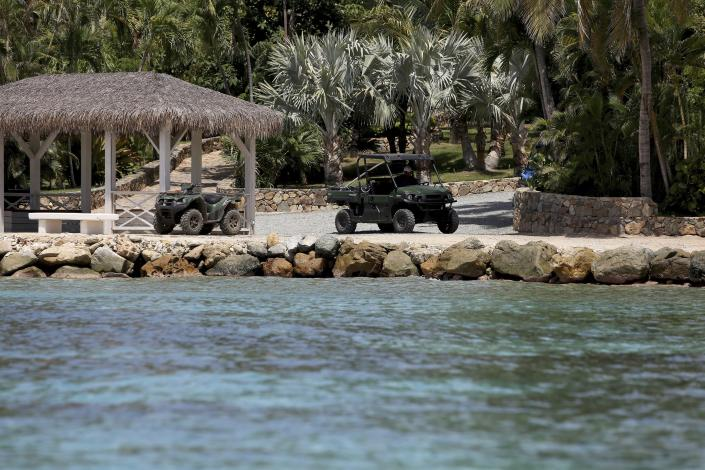 A man drives a utility task vehicle on Little St. James Island, in the U. S. Virgin Islands, a property owned by Jeffrey Epstein, Wednesday, Aug. 14, 2019. Only a handful of Epstein's employees were seen kicking up dust as they drove around in UTV's on an island that once boasted dozens of workers and several armed security guards. (AP Photo/Gabriel Lopez Albarran)
