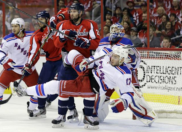 New York Rangers defenseman John Moore (17) falls with Washington Capitals right wing Troy Brouwer (20) and goalie Henrik Lundqvist (30), from Sweden, nearby, in the first period, of Game 7 first-round NHL Stanley Cup playoff hockey series, Monday, May 13, 2013 in Washington. (AP Photo/Alex Brandon)