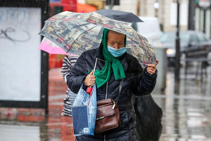 An elderly woman wearing a face mask shelters from the rain in London. (Getty)