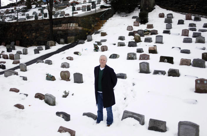 """FILE - In this file photo of Jan. 19, 2011 photo, Ed Martin Jr., director of the Hartsdale Pet Cemetery, stands in the cemetery in Hartsdale, N.Y., the first burial ground for animals named to the National Register of Historic Places. The 116-year-old Hartsdale Pet Cemetery, final home to some 75,000 animals and a few hundred humans, is being designated for its """"social history and landscape architecture."""" (AP Photo/Seth Wenig, File)"""