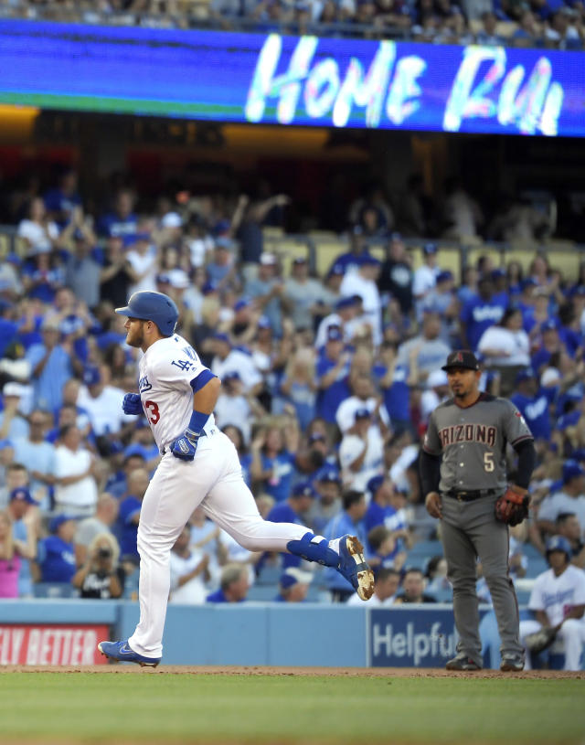 Los Angeles Dodgers' Max Muncy, left, rounds third as he passes Arizona Diamondbacks third baseman Eduardo Escobar after hitting a solo home run during the second inning of a baseball game Saturday, Aug. 10, 2019, in Los Angeles. (AP Photo/Mark J. Terrill)