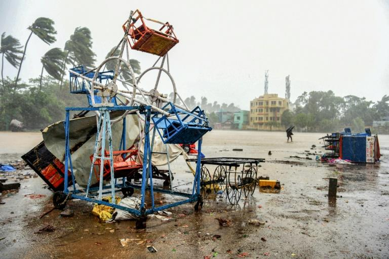 A man walks past a small, damaged Ferris wheel at the beach in the town of Alibag