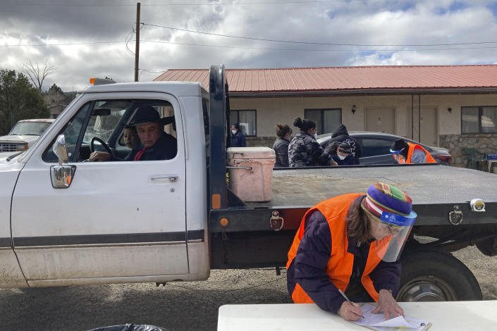 Motorists including Elmer Serna, in driver's seat, awaited vaccine shots as medical workers complete paperwork at a drive-thru immunization clinic at a motor inn in Mora, N.M., on Tuesday, April 20, 2021. New Mexico is among the states with the highest rates of vaccination for COVID-19 and efforts are underway to respond to skepticism and misinformation about the effectiveness and risks of immunization. First Lady Jill Biden was kicking off a visit to the U.S. Southwest with a tour of a vaccination clinic in Albuquerque. (AP Photo/Morgan Lee)