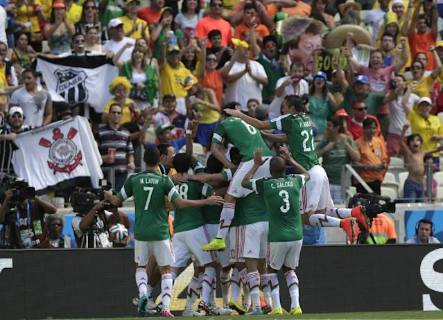 Mexico players celebrate after scoring the opening goal during the World Cup round of 16 soccer match between the Netherlands and Mexico at the Arena Castelao in Fortaleza, Brazil, Sunday, June 29, 2014. (AP Photo/Marcio Jose Sanchez)
