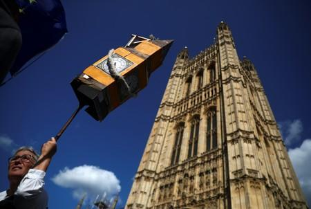 An anti-Brexit protester holds up a prop Big Ben outside the Houses of the Parliament in London
