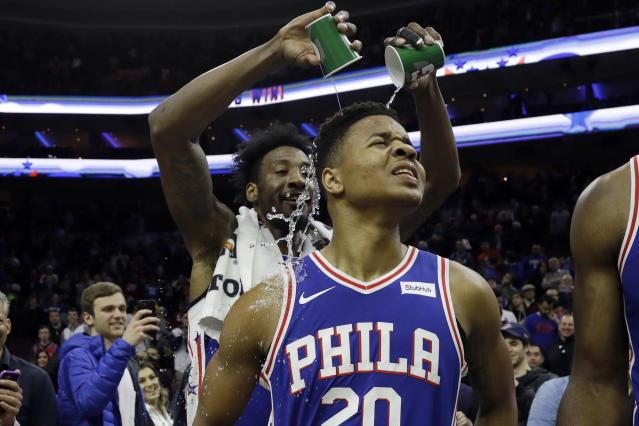 Robert Covington, back, helps Markelle Fultz celebrate his return to the court Monday night. (AP)