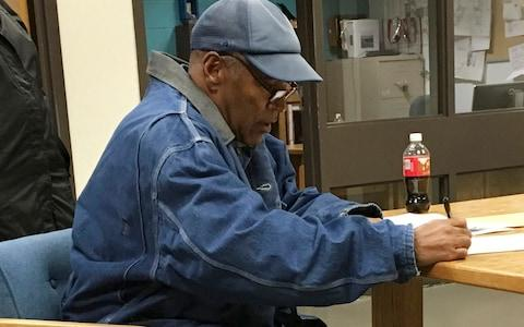 Former football legend O.J. Simpson signs documents at the Lovelock Correctional Center - Credit: AP