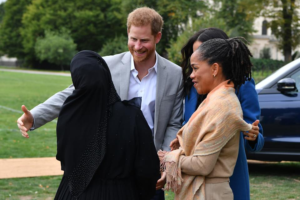 LONDON, ENGLAND - SEPTEMBER 20: Prince Harry, Duke of Sussex, Meghan, Duchess of Sussex and her mother, Doria Ragland are greeted by Zahira Ghaswala (L), Hubb community kitchen coordinator, during an event to mark the launch of a cookbook with recipes from a group of women affected by the Grenfell Tower fire at Kensington Palace on September 20, 2018 in London, England. (Photo by Ben Stansall - WPA Pool/Getty Images)