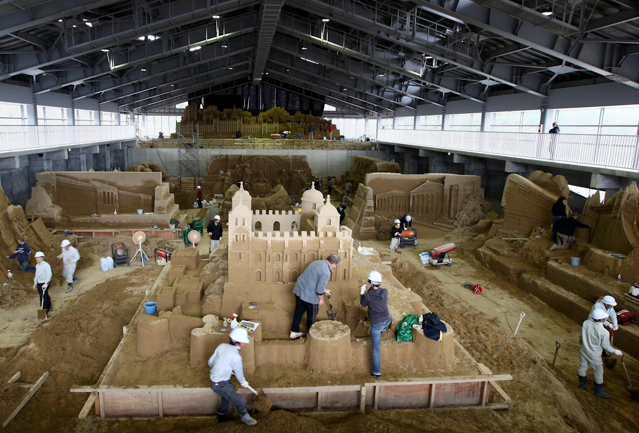 Sand sculptors finish a sand replicas at Sand Museum located in the Tottori Dune on April 1, 2012 in Tottori, Japan. (Photo by Buddhika Weerasinghe/Getty Images)