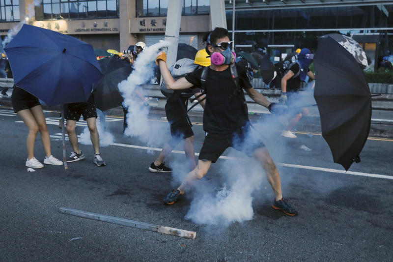 A protester throws a tear gas canister which was fired by police as they face off with riot police on streets in Hong Kong, Sunday, July 28, 2019. Police launched tear gas at protesters in Hong Kong on Sunday for the second night in a row in another escalation of weeks-long anti-government and pro-democracy protests in the semi-autonomous Chinese territory. (AP Photo/Vincent Yu)