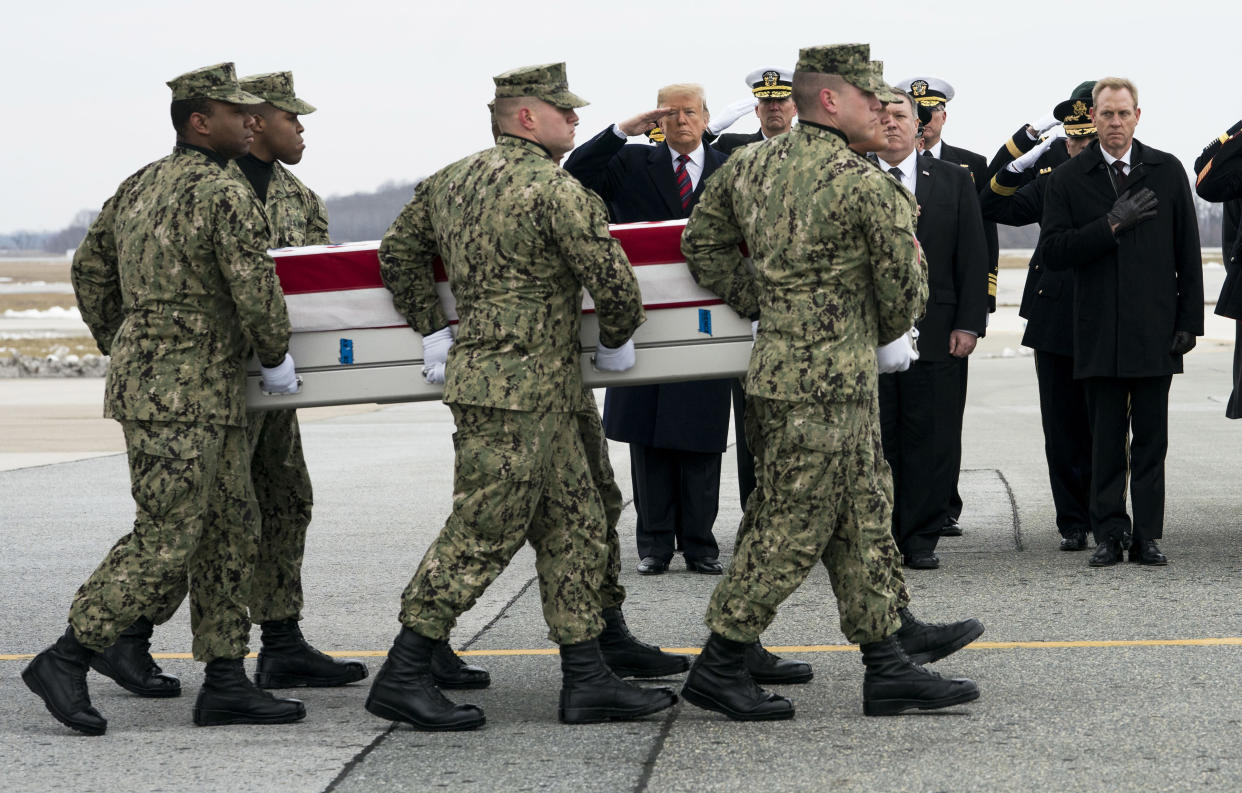 President Donald Trump looks on as military servicemen carry the remains of Scott A. Wirtz, one of four Americans killed in a suicide bombing in Syria, at Dover Air Force Base in Delaware.