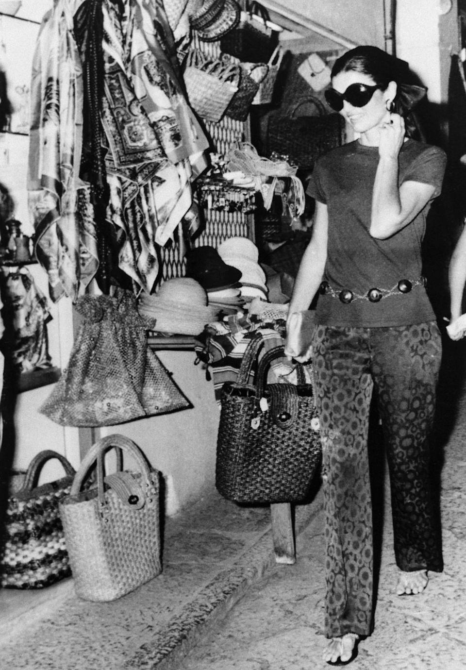 <p>Jackie, while shopping on holiday in southern Italy, wears patterned pants, chic leather sandals, and a draped belt. Oversize sunglasses, hoop earrings, and sandals complete the casual look.<br></p>
