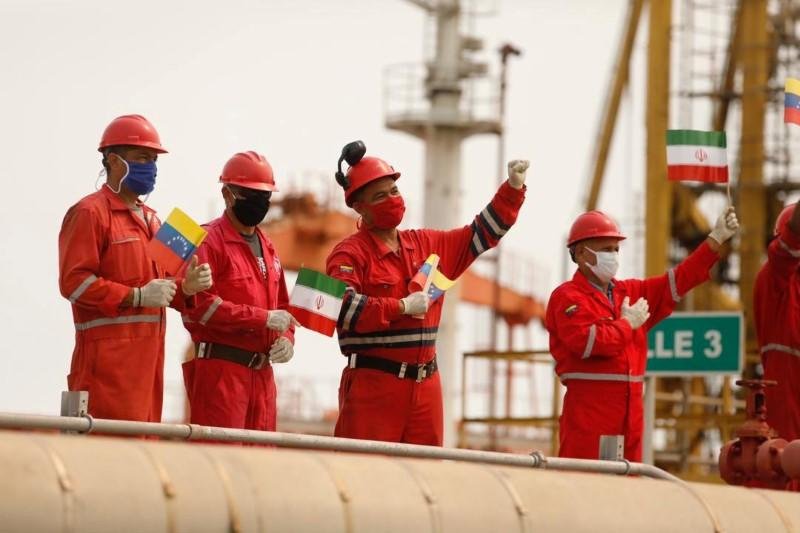 """Workers of the state-oil company Pdvsa holding Iranian and Venezuelan flags greet during the arrival of the Iranian tanker ship """"Fortune"""" at El Palito refinery in Puerto Cabello"""