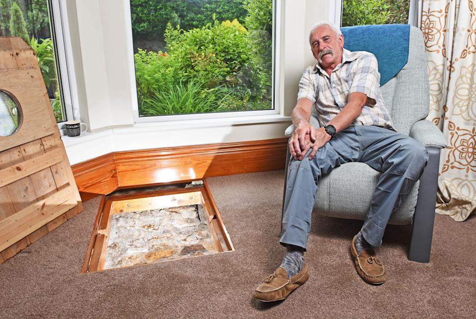 CATERS NEWS (PICTURED - Colin Steer sitting beside the well in his living room) - A grandad has spent the last decade digging out a 17ft deep medieval well in his living room after noticing a slight dip in the floor when redecorating. Colin Steer, from Plymouth, discovered the well after he noticed a dip in the floor while redecorating his living room ten years ago and has since spent the last decade digging out the 17ft well. The 70-year-old believes that the well could date back to medieval times after discovering an old sword while digging out the well and plans of the site suggests that the well could date back to the 1500s. Colin said: