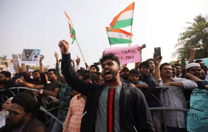 Demonstrators hold placards and shout slogans during a protest against a new citizenship law in Mumbai