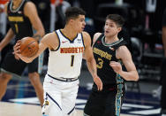 Denver Nuggets forward Michael Porter Jr., left, looks to pass the ball as Memphis Grizzlies guard Grayson Allen defends in the first half of an NBA basketball game Monday, April 26, 2021, in Denver. (AP Photo/David Zalubowski)