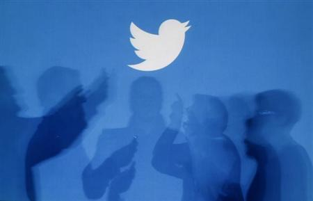 Shadows of people holding mobile phones are cast onto a backdrop projected with the Twitter logo in Warsaw