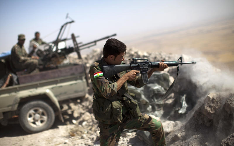 An Iraqi Kurdish Peshmerga fighter fires at Islamic-State (IS) militant positions, from his position on the top of Mount Zardak, a strategic point taken 3 days ago, about 25 kilometres east of Mosul on September 9, 2014