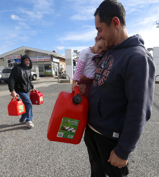 Chris Ferrone, right, carries his 3-year-old daughter Kora as she holds on to a five-gallon gas can while waiting in line to fill up at a gas station in Toms River, N.J. Thursday, Nov. 1, 2012. Motorists across New Jersey faced a second day of stressful, enormous lines Thursday at the gas stations that still had both electricity and supplies, as power outages kept many pumps out of service and tough travel made fuel deliveries difficult. (AP Photo/Julio Cortez)