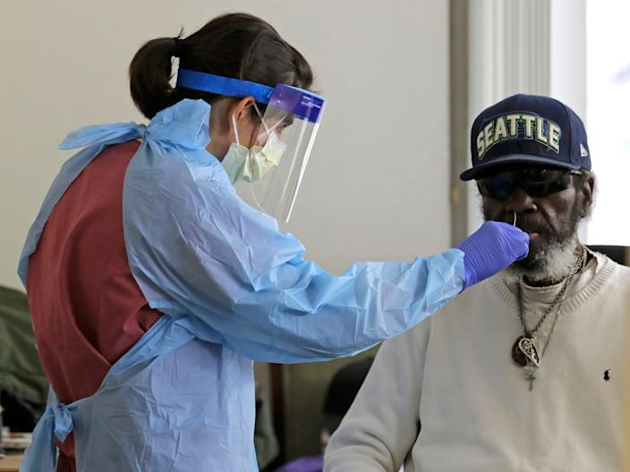 Dr. Gabrielle Beger takes a nose-swab sample from Lawrence McGee as she conducts tests for the coronavirus at Queen Anne Healthcare, a nursing and rehabilitation facility in Seattle, Washington, on April 17, 2020.
