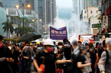 FILE PHOTO : Anti-extradition bill protesters run as riot police fire tear gas during a protest in Hong Kong