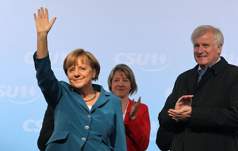 In this picture taken Wednesday, Sept. 11, 2013, German Chancellor Angela Merkel, left, waves next to governor of Bavaria and top candidate of the CSU Horst Seehofer, right, during an election campaign of the Christian Democratic Party, CDU, and the Christian Social Union in Bavaria, CSU, in Miesbach, Germany. Merkel's conservatives hope to add momentum to the German leader's quest for a third term with a big state election win on Sunday in prosperous Bavaria — just a week before the whole country goes to the polls. (AP Photo/dpa, Marc Mueller)