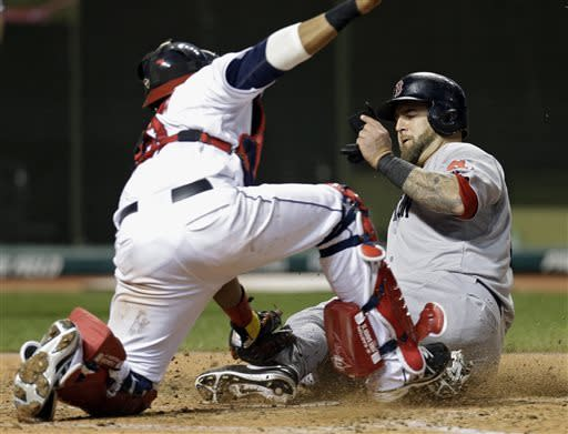 Boston Red Sox's Mike Napoli, right, beats the tag by Cleveland Indians catcher Carlos Santana to score from second on a single by Mike Carp in the seventh inning of a baseball game on Thursday, April 18, 2013, in Cleveland. (AP Photo/Mark Duncan)
