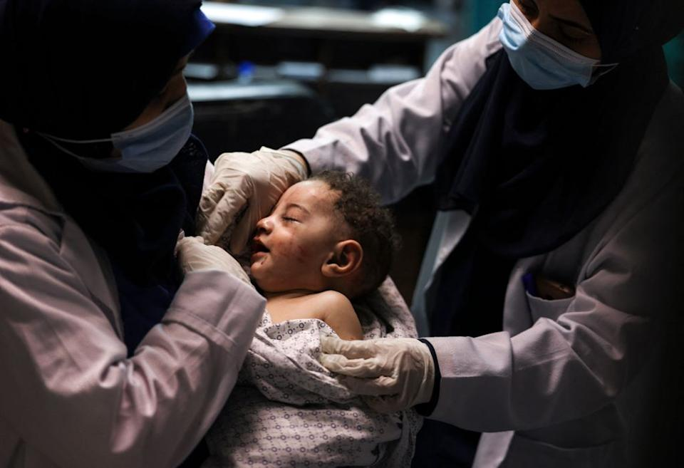 The baby boy, named as Omar, in the arms of two nurses wearing face masks.