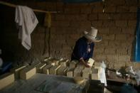 Luceli Banda Medina, a former student of Peru's presidential candidate Pedro Castillo, arranges blocks of cheese that she and her family made at home, in Puna