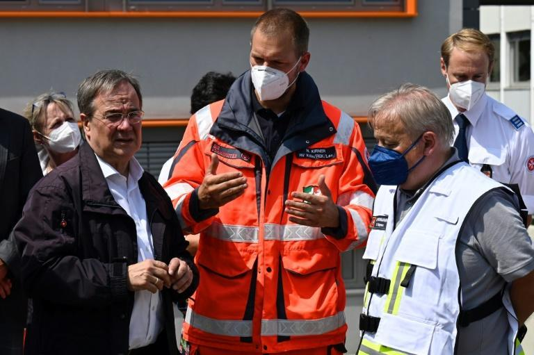 Armin Laschet (L) was spotted laughing during a visit to a flood-hit town