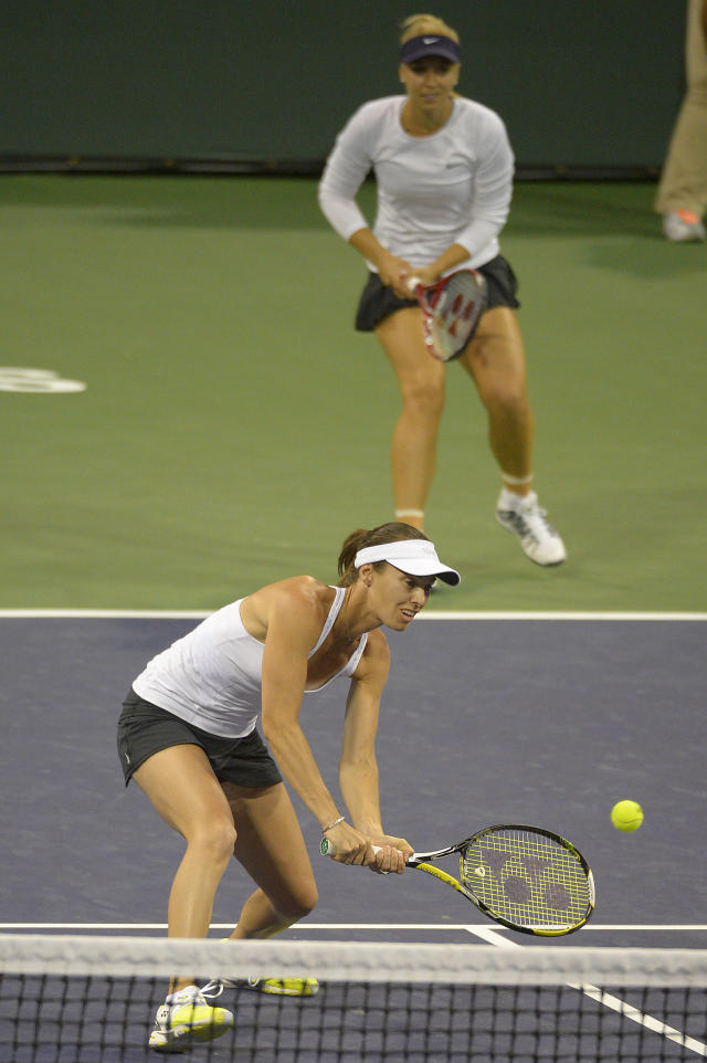 Martina Hingis, of Switzerland, foreground, returns a shot in front of her partner Sabine Lisicki, of Germany, as they compete against Ashleigh Barty, of Australia, and Casey Dellacqua, of Australia, during a first round doubles match at the BNP Paribas Open tennis tournament, Thursday, March 6, 2014, in Indian Wells, Calif. (AP Photo/Mark J. Terrill)