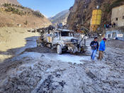 People inspect the site near the damaged Dhauliganga hydropower project at Reni village in Chamoli district after a portion of Nanda Devi glacier broke off in Tapovan area of the northern state of Uttarakhand, Sunday, Feb.7, 2021. (AP Photo)
