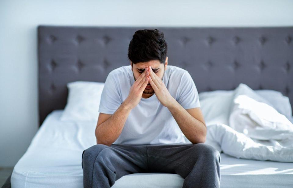 Man sitting on bed holding his head.