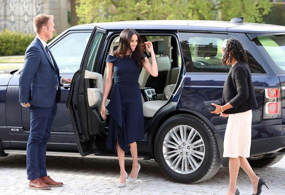 "<p>Markle wore a <a class=""link rapid-noclick-resp"" href=""http://meghansmirror.com/royal-style/royal-wedding/meghan-markle-doria-ragland-check-in-to-cliveden-house-hotel/"" rel=""nofollow noopener"" target=""_blank"" data-ylk=""slk:navy blue Roland Mouret dress"">navy blue Roland Mouret dress</a> and gray suede Manolo Blahnik pumps to her arrival at <a href=""https://www.townandcountrymag.com/leisure/travel-guide/a9035896/cliveden-house/"" rel=""nofollow noopener"" target=""_blank"" data-ylk=""slk:Cliveden House"" class=""link rapid-noclick-resp"">Cliveden House</a>, where she'll be staying the night before the wedding. </p>"