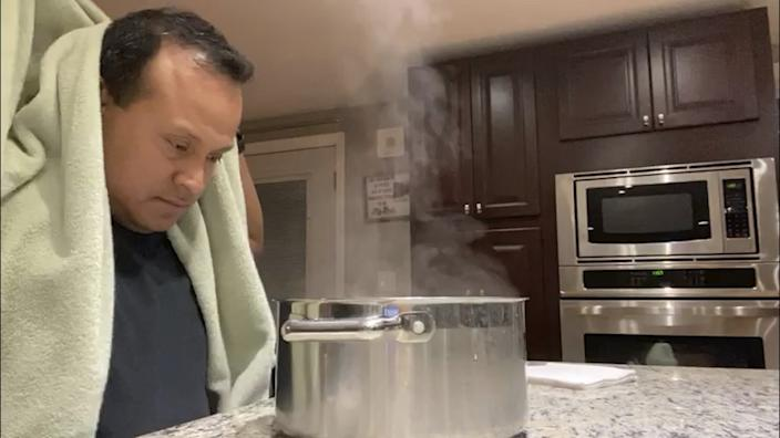 Alex Melo uses a steaming pot for a nebulizing treatment at his home in York, Maine.