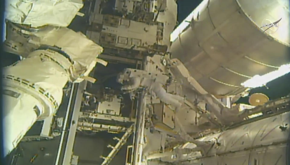 This photo provided by NASA, astronauts Andrew Morgan and Nick Hague (not seen) begin to install a docking port delivered by SpaceX last month outside the International Space Station on Wednesday, Aug. 21, 2019. The port will be used by SpaceX and Boeing once they start launching astronauts to the orbiting lab late this year or early next year. (NASA via AP)