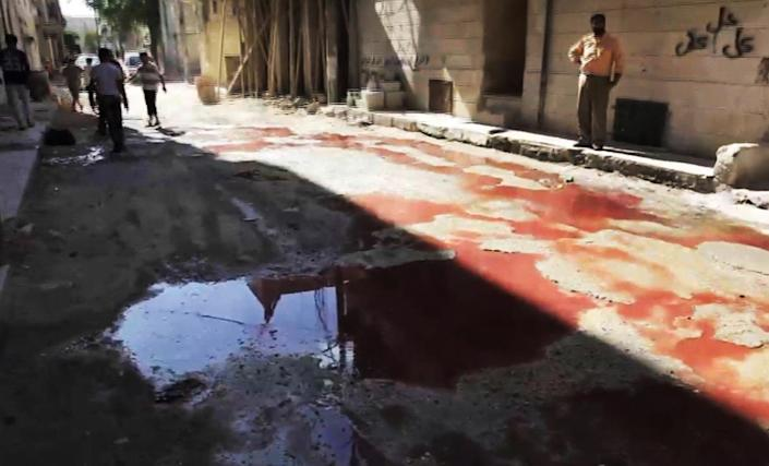 This image taken from video filmed by an independent cameraman and made available on Tuesday, Sept. 4, 2012 shows pools of blood on a road in Myasar neighborhood, Aleppo, Syria. Government jets bombed the residential area of Myasar, reducing many of its buildings to rubble and causing a huge fire. (AP Photo/APTN)