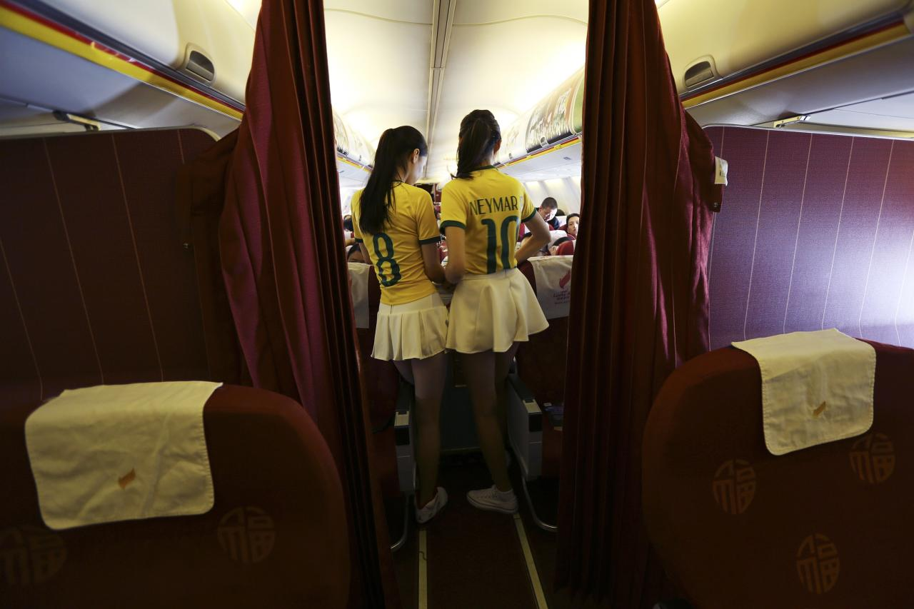 Flight attendants wearing Brazil soccer team jerseys prepare to serve the passengers on an airplane travelling from Kunming to Hangzhou June 23, 2014. A Chinese airline company renovated the cabin of one of its flights then dressed the flight attendants with soccer jerseys as a way to celebrate the 2014 Brazil World Cup and hoping to attract more customers, local media reported. REUTERS/Wong Campion (CHINA - Tags: SPORT SOCCER WORLD CUP SOCIETY TRANSPORT)