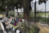 A stray dog sleeps on a sidewalk as former diplomat Virendra Gupta, far right, and his singer wife Veena Gupta teach underprivileged children in New Delhi, India, on, Sept. 3, 2020. The Indian couple are conducting free classes for underprivileged children on a sidewalk in New Delhi with the goal to keep them learning and not left behind when schools reopen. As most schools in India remain shut since late March when the country imposed a nationwide lockdown to curb the spread of COVID-19, many switched to digital learning and taking classes online. (AP Photo/Manish Swarup)