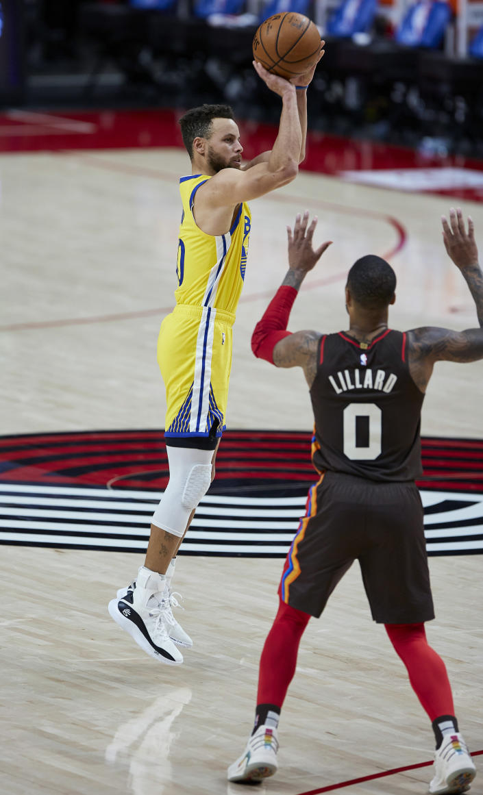Golden State Warriors guard Stephen Curry shoots a 3-point basket over Portland Trail Blazers guard Damian Lillard during the first half of an NBA basketball game in Portland, Ore., Wednesday, March 3, 2021. (AP Photo/Craig Mitchelldyer)