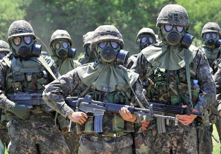 South Korean soldiers wearing gas masks take part in a training exercise in in Yeoncheon, May 16, 2013. Military service is taken extremely seriously South Korea, which remains technically at war with North Korea because their 1950-53 conflict ended with a ceasefire rather than a peace treaty