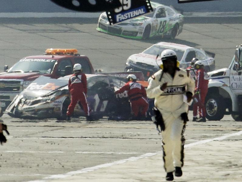 Rescue workers tend to the wreckage of the No. 11 FedEx Express Toyota driven by Denny Hamlin after he collided with Joey Logano on the final lap of the NASCAR Sprint Cup series auto race in Fontana, Calif., Sunday March 24, 2013. The pair had been battling for the lead the last three laps. The No. 18 car of Kyle Busch passes behind on its vicory lap. (AP Photo/Reed Saxon)