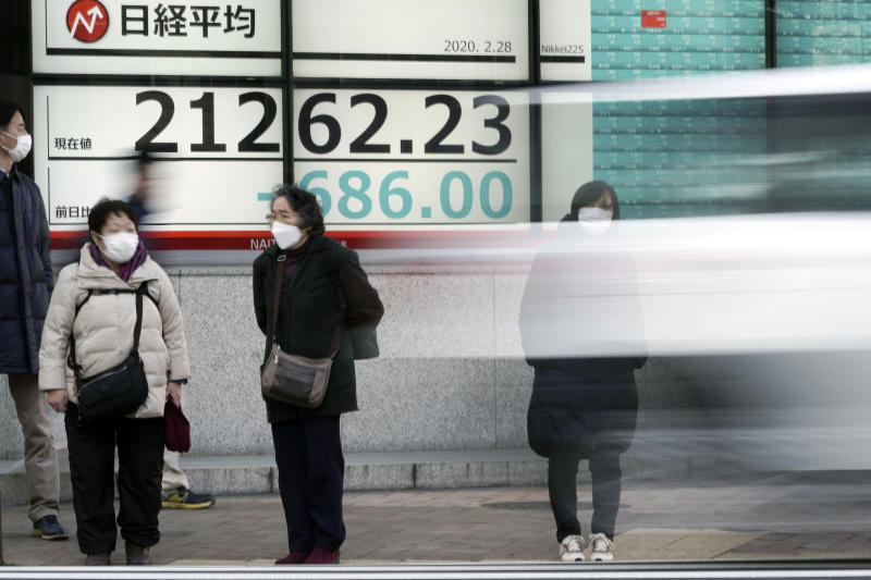 Pedestrians stand in front of an electronic stock board showing Japan's Nikkei 225 index at a securities firm in Tokyo Friday, Feb. 28, 2020. Asian stock markets have fallen further on virus fears after Wall Street endured its biggest one-day drop in nine years. (AP Photo/Eugene Hoshiko)