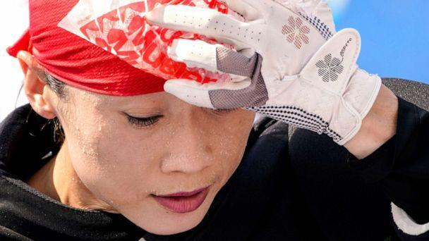PHOTO: Beads of sweat gather on the face of China women's field hockey goalkeeper Dongxiao Li as she presses a bag of ice against her head during practice hours at the 2020 Summer Olympics, July 23, 2021, in Tokyo. (John Minchillo/AP)