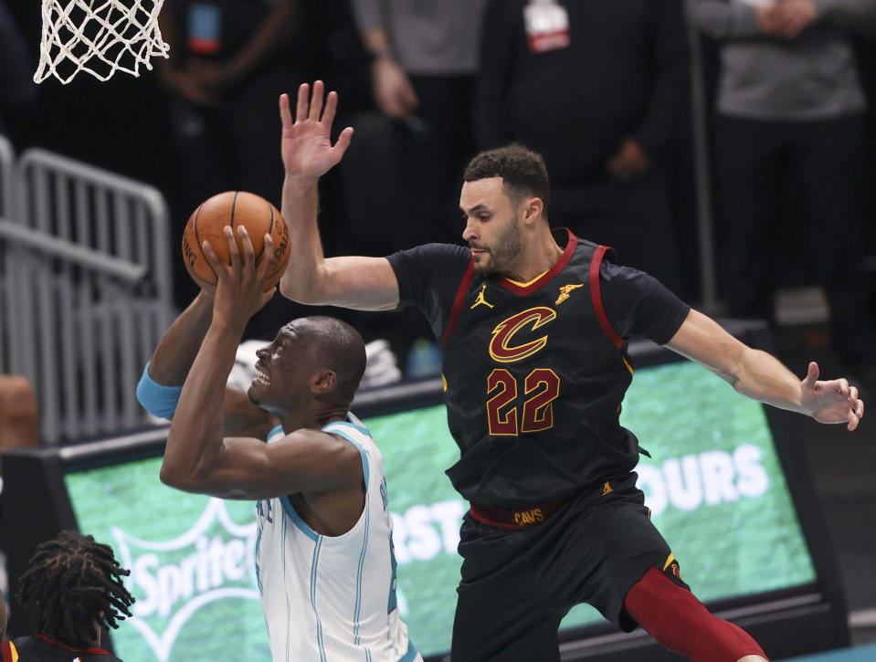 Charlotte Hornets center Bismack Biyombo, left, is fouled by Cleveland Cavaliers forward Larry Nance Jr. (22) as he drives to the basket during the second quarter of an NBA basketball game in Charlotte, N.C., Wednesday, April 14, 2021. (AP Photo/Nell Redmond)