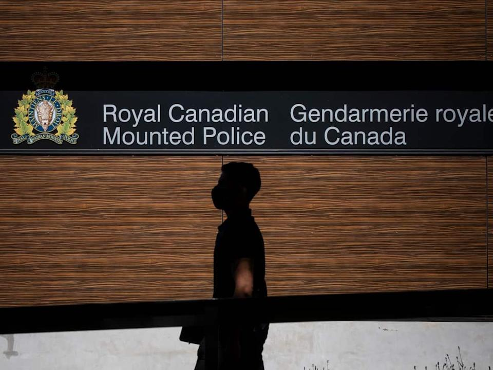 A man walks by a sign outside of the RCMP