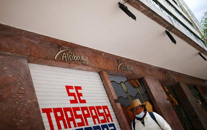 A man wearing a face mask passes in front of a closed store with a business transfer sign during the start of the gradual reopening of commercial activities in downtown Mexico City - EDGARD GARRIDO /REUTERS